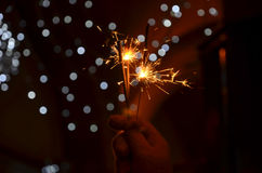 New years eve celebration with hand held sparkler fireworks. Hand with glove holding sparkler firework on new year's eve with bokeh on background royalty free stock images