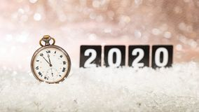 2020 New Years eve celebration. Minutes to midnight on an old watch, bokeh festive. Background stock photo