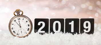 2019 New Years eve celebration. Minutes to midnight on an old watch, bokeh festive background. Banner stock image