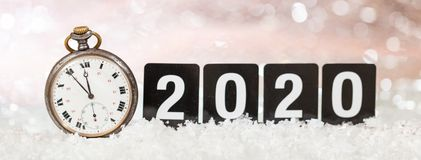 2020 New Years eve celebration. Minutes to midnight on an old watch, bokeh festive background. Banner stock image