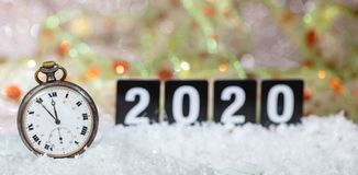 2020 New Years eve celebration. Minutes to midnight on an old watch, bokeh festive background. Banner stock photo