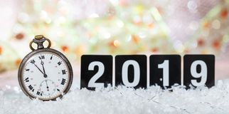 2019 New Years eve celebration. Minutes to midnight on an old watch, bokeh festive background. Banner royalty free stock image