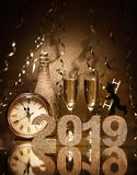New Years Eve celebration. Background with pair of flutes, bottle of champagne, clock and a chimney sweep as lucky charm royalty free stock photography