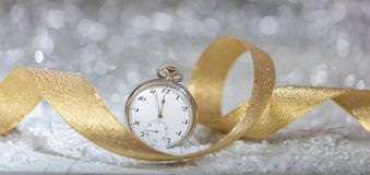 New Years eve celebration party. Minutes to midnight on an old watch, bokeh festive background. Banner royalty free stock image