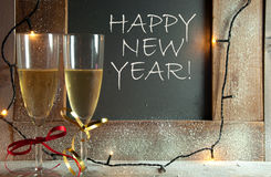 New years eve celebration. Two champagne glasses next to chalkboard with happy new year greeting royalty free stock images