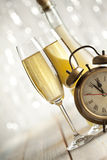 New Years Eve - champagne and alarm clock. On silver background Stock Photos