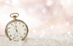 New Years eve countdown. Minutes to midnight on an old fashioned pocket watch, bokeh snowy background. Copy space royalty free stock photography