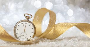 New Years eve countdown. Minutes to midnight on an old watch, bokeh festive background. Banner stock photography