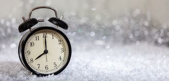 New Years eve countdown. Minutes to midnight on a vintage alarm clock. Banner, copy space stock images