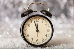 New Years eve countdown. Minutes to midnight on a vintage alarm clock. Closeup view stock photo