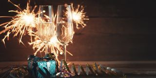 New years eve background. New years eve decoration with champaign glasses and burning sparkler stock image