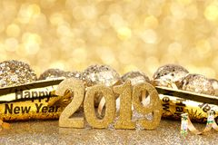 New Years Eve 2019 decorations with twinkling background. New Years Eve 2019 golden numbers and decorations with twinkling light background royalty free stock image