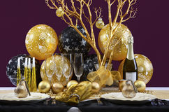 New Years Eve Dinner Table Setting. Happy New Years Eve elegant dinner table setting with black and gold decorations, balloons and stylish centerpiece Royalty Free Stock Image