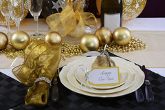New Years Eve Dinner Table Setting. Happy New Years Eve elegant dinner table setting with black and gold decorations, balloons and stylish centerpiece, close up Royalty Free Stock Photo