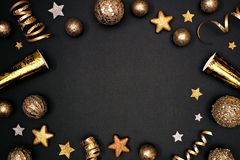New Years Eve frame of glittery gold stars, streamers, decorations and noisemakers, above view on a black background