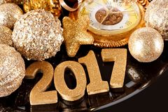 New Years Eve 2017 golden numbers with decorations on black. New Years Eve 2017 golden numbers surrounded by shiny decorations on black charger Royalty Free Stock Photography