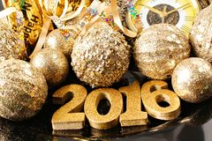 New Years Eve 2016 golden numbers and decorations. New Years Eve 2016 golden numbers surrounded by shiny decorations Royalty Free Stock Photos