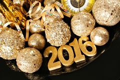 New Years Eve 2016 golden numbers and decorations. New Years Eve 2016 golden numbers surrounded by shiny decorations Royalty Free Stock Image
