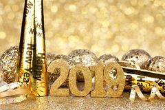 New Years Eve 2019 decorations with twinkling background. New Years Eve 2019 golden numbers and decorations with twinkling light background stock photo