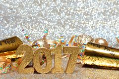 New Years Eve 2017 numbers and decorations with twinkling background. New Years Eve 2017 golden numbers and decorations with twinkling light background Royalty Free Stock Photo