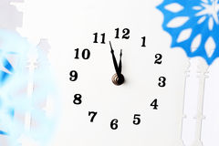 A New Years Eve. Paper snowflakes and clock. A New Years Eve Royalty Free Stock Photography