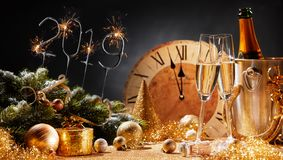 New Years Eve 2019 party background. With flutes of champagne, decorations, and a clock counting down to midnight stock images