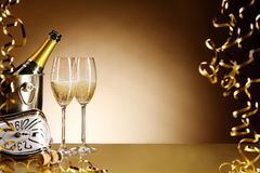 New Years Eve party celebration background. With chilled champagne on ice and two elegant flutes, gold streamers and a stylish clock counting down to midnight