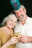 New Years Eve Toast. Beautiful senior couple toasting in the New Year with champagne.  Black background Stock Photography