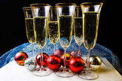 New years glasses and toys on the table. Christmas glasses, Champagne, new years toys on the table. The black background. New year card. Christmas picture Royalty Free Stock Image