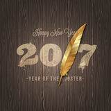 New years greeting with golden rooster feather Stock Photography