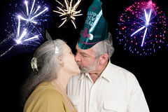 New Years Kiss at Midnight. Beautiful senior couple at a New Year's party kisses at the stroke of midnight as the fireworks go off in the background Stock Photo