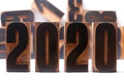 New Years 2020, Letterpress wooden type numbers. 2020 in wooden letterpress type isolated on white and blurry types in background royalty free stock images