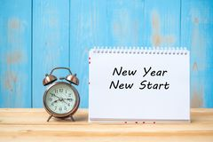 New years New Start text on notebook and retro alarm clock on table and copy space. stock image
