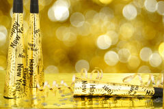 New Years party. New Years Eve noisemakers and confetti with twinkling gold light background Stock Photography