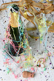 New Years Party Aftermath. High angle shot of a Champagne bottle, streamers and confetti after a New Years Eve Party. Vertical format with shallow depth of field Stock Image