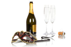 New Years party with bottle of champagne. Bottle of champagne with two flutes and party mask Stock Photos