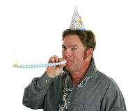 New Years Party Guy. A happy guy at a new years eve party blowing a noisemaker and wearing a party hat Stock Images