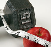 New Years Resolution. Resolving to lose weight by diet and exercise, apple, weights, and a measuring tape Royalty Free Stock Photos