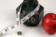 New Years Resolution. Resolving to lose weight by diet and exercise, apple, weights, and a measuring tape royalty free stock photography