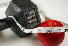 New Years Resolution. Resolving to lose weight by diet and exercise, apple, weights, and a measuring tape stock photos