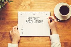 New years resolution with a person holding a pen. On a wooden desk royalty free stock photography