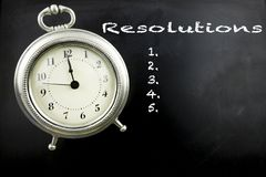 New Years resolutions on chalkboard. Pewter antique alarm clock with Resolutions on blackboard with copy space stock illustration