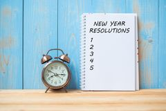 New years Resolutions text on notebook and retro alarm clock on table and copy space. Goals, Mission and New Start Concept stock photography