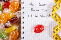 New years resolutions written in notebook, candies and tape measure Royalty Free Stock Photos
