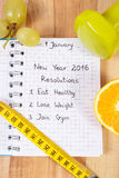 New years resolutions written in notebook and dumbbells with centimeter Stock Photos
