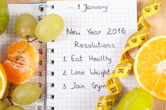 New years resolutions written in notebook and fruits, dumbbells with centimeter Stock Photography