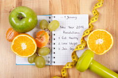 New years resolutions written in notebook and fruits, dumbbells with centimeter Stock Photos