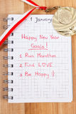 New years resolutions written in notebook and gold medal Stock Photo