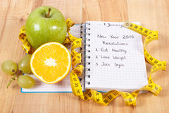 New years resolutions written in notebook and tape measure Stock Image