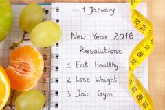 New years resolutions written in notebook and tape measure Royalty Free Stock Images